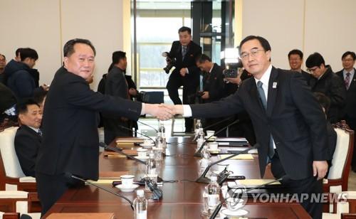 Le ministre sud-coréen de l'Unification et le chef de la délégation sud-coréenne Cho Myoung-gyon échange une poignée de main avec son homologue nord-coréen Ri Son-gwon avant le début des pourparlers de haut niveau le 9 janvier 2018