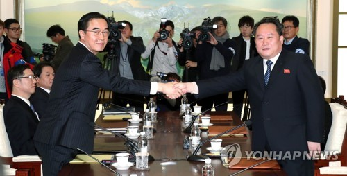 Le ministre sud-coréen de l'Unification et le chef de la délégation sud-coréenne Cho Myoung-gyon (à droite) échange une poignée de main avec son homologue nord-coréen Ri Son-gwon avant le début des pourparlers de haut niveau le 9 janvier 2018.