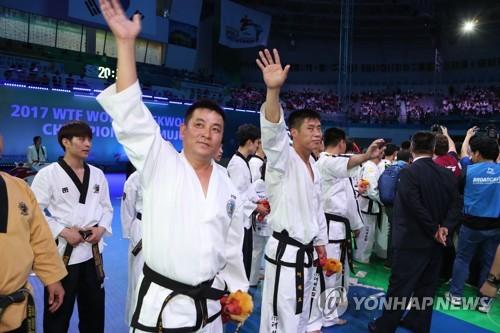 Des taekwondoïstes nord-coréens saluent la foule lors de la cérémonie de clôture des Championnats du monde de taekwondo à Muju en Corée du Sud le 30 juin 2017.