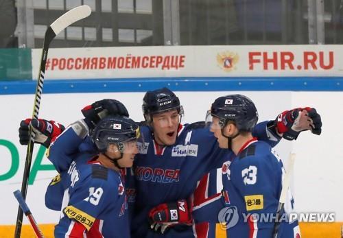 Sur cette photo datant du 16 décembre 2017, l'attaquant sud-coréen Mike Testwuide (au c.) célèbre son but contre la Suède avec ses coéquipiers Kim Sang-wook (à g.) et Eric Regan à la Channel One Cup au VTB Ice Palace à Moscou. (Reuters)