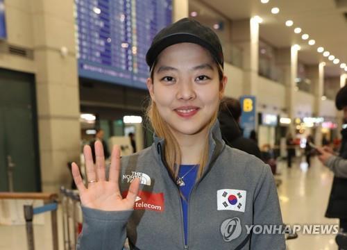 Sur cette photo prise le 12 décembre 2017, la patineuse de vitesse sud-coréenne Kim Bo-reum salue les photographes à l'aéroport international d'Incheon après son retour de Salt Lake City, où elle a participé à une épreuve de Coupe du monde de l'ISU.