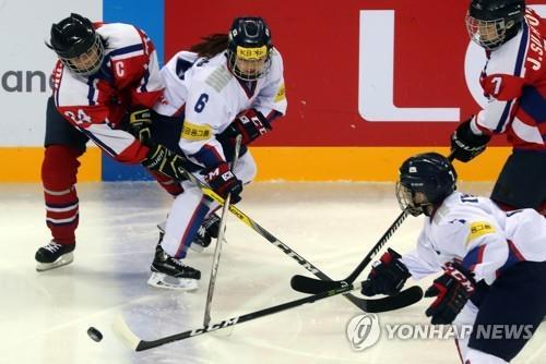 Sur cette photo prise le 6 avril 2017, des joueuses de hockey sud-coréennes et nord-coréennes, en blanc et en rouge respectivement, s'affrontent lors d'un match du groupe A, division II du Championnat du monde féminin de la Fédération internationale de hockey sur glace (IIHF) à Gangneung, dans la province du Gangwon.