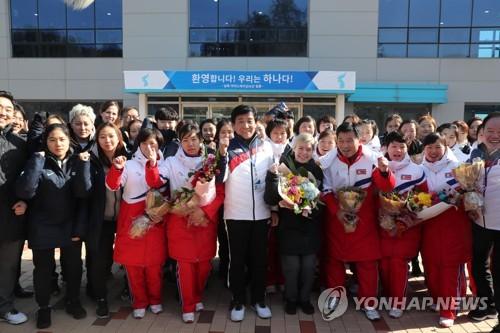 Les membres des équipes sud et nord-coréennes de hockey sur glace posent pour une photo lors de la cérémonie d'accueil au Centre national d'entraînement de Jincheon ce jeudi 25 janvier 2018.