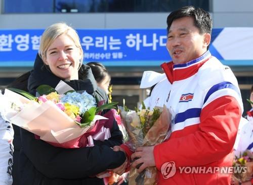 L'entraîneuse de l'équipe sud-coréenne Sarah Murray échange une poignée de main avec son homologue nord-coréen Pak Chol-ho.