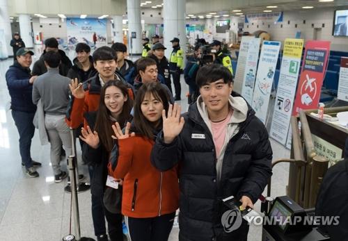 Des skieurs sud-coréens saluent de la main à l'aéroport international de Yangyang le mercredi 31 janvier 2018, avant de se diriger vers la station de ski du col Masik, en Corée du Nord.