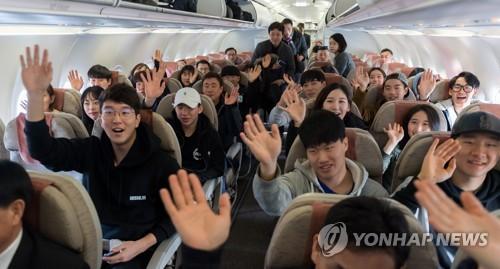 Des skieurs sud-coréens saluent de la main les journalistes dans un avion à l'aéroport international de Yangyang, dans la province du Gangwon, le mercredi 31 janvier 2018, avant de se diriger vers Wonsan, ville nord-coréenne, pour effectuer des entraînements conjoints avec des athlètes nord-coréens à la station de ski du col Masik. (Joint Press Corps-Yonhap)