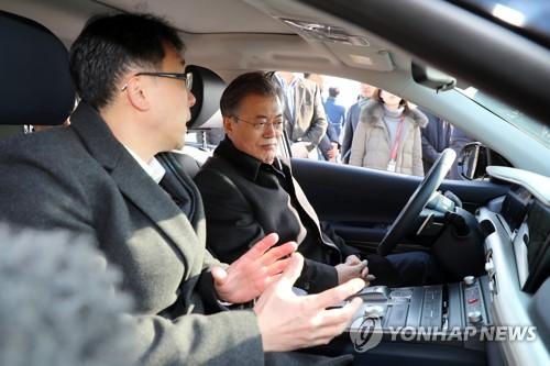 Le président Moon Jae-in (à droite) écoute un responsable de Hyundai Motor expliquant comment manier une voiture autonome à pile à combustible le 2 février 2018 sur l'autoroute reliant Séoul à Busan.