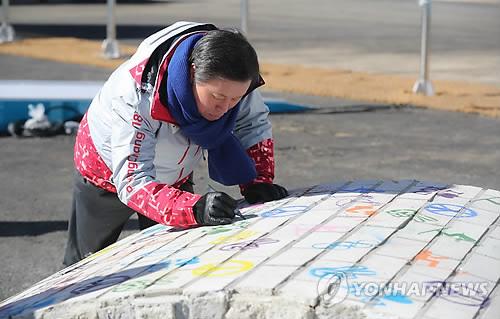 Do Jong-hwan, le ministre de la Culture, du Sport et du Tourisme, appose sa signature sur le mur de la trêve le lundi 5 février 2018 lors de la cérémonie de dévoilement.