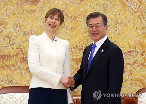 Le président sud-coréen Moon Jae-in et la présidente estonienne Kersti Kaljulaid échangent une poignée de main le 6 février 2018 avant d'entamer leur sommet à Cheong Wa Dae.