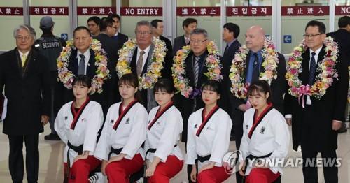 Des membres de l'équipe de démonstration de taekwondo nord-coréenne et des officiels à l'aéroport international de Gimpo le 7 février 2018.