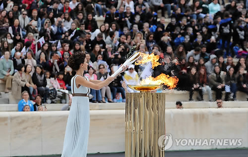 La grande prêtresse Katerina Lehou allume la flamme au chaudron au Stade panathénaïque à Athènes, en Grèce, le mardi 31 octobre 2017 lors de la cérémonie de remise de la flamme des Jeux olympiques d'hiver de PyeongChang 2018.