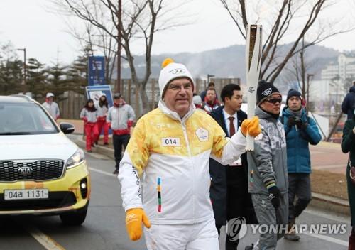 Le président du CIO Thomas Bach porte la torche olympique le 9 février 2018 au Alpensia Resort à PyeongChang.