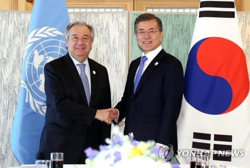 Le président Moon Jae-in échange une poignée de main avec le secrétaire général des Nations unies (ONU) Antonio Guterres à Gangneung, dans la province du Gangwon, avant leur réunion bilatérale.