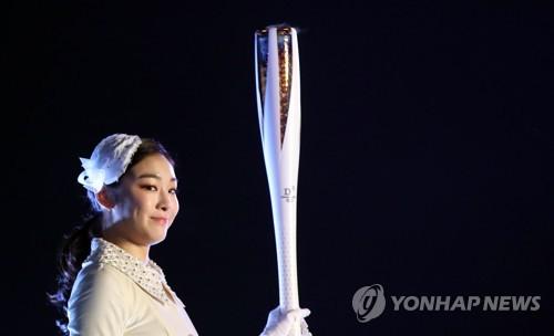 L'ancienne championne olympique de patinage artistique Kim Yu-na porte la flamme olympique avant d'allumer le chaudron au stade olympique de PyeongChang à PyeongChang, ce vendredi 9 février 2018.