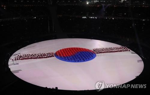 Des participants à la cérémonie forment le Taegeukgi, le drapeau national sud-coréen.