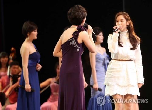 Des chanteuses nord-coréennes et Seohyun (2e à partir de la dr.), membre du groupe Girls' Generation, chantent ensemble le dimanche 11 février 2018 au Théâtre national de Corée à Séoul, lors du concert de la troupe artistique nord-coréenne Samjiyon.