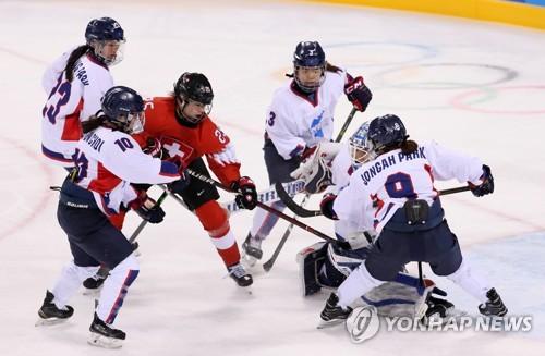 Les joueuses de hockey de l'équipe coréenne unifiée et la Suissesse Alina Muller le 10 février 2018 au centre de hockey de Kwandong à Gangneung.