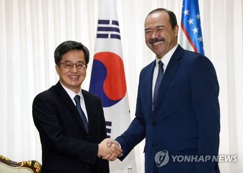 Le ministre sud-coréen de la Stratégie et des Finances, Kim Dong-yeon (à gauche), échange une poignée de main avec le Premier ministre ouzbek Abdulla Aripov, le mardi 13 février 2018 à Tachkent, lors de la première réunion économique bilatérale de haut niveau.