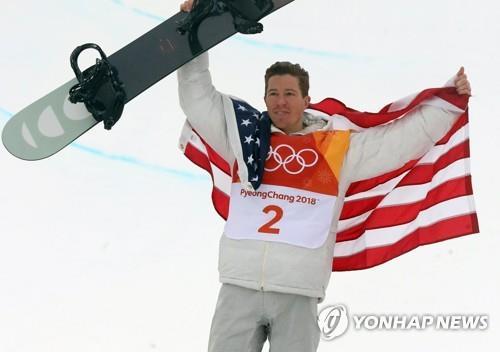 Le snowboardeur américain Shaun White pose devant les photographes lors de la cérémonie des fleurs après avoir remporté la médaille d'or en halfpipe au parc à neige de Phoenix lors des Jeux olympiques d'hiver de PyeongChang, le 14 février 2018.