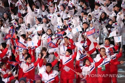 Les athlètes nord-coréens (en rouge) et sud-coréens (en blanc) défilent ensemble à la cérémonie de clôture à PyeongChang.