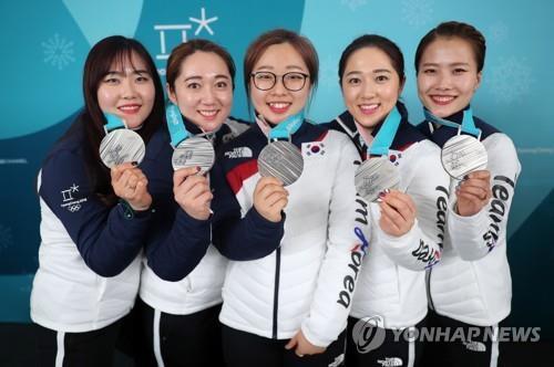 Les membres de l'équipe féminine de curling avec leur médaille d'argent.