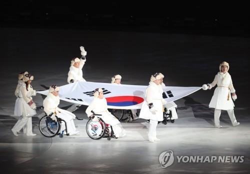 Des athlètes paralympiques sud-coréens portent le drapeau national lors de la cérémonie d'ouverture.