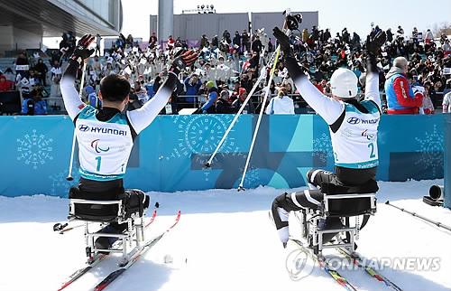 Les Nord-Coréens Ma Yu-chol (à droite) et Kim Jong-hyon saluent la foule après avoir fini la course du 15km assis au centre de biathlon d'Alpensia à PyeongChang le dimanche 11 mars 2018.