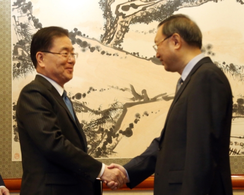 Le conseiller présidentiel à la sécurité nationale Chung Eui-yong échange une poignée de main le 12 mars 2018 avec le conseiller d'Etat chinois, Yang Jiechi, à Pékin, en Chine.