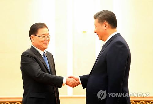 Le conseiller présidentiel à la sécurité nationale Chung Eui-yong (à gauche) échange une poignée de main le 12 mars 2018 à Pékin avec le président chinois Xi Jinping.