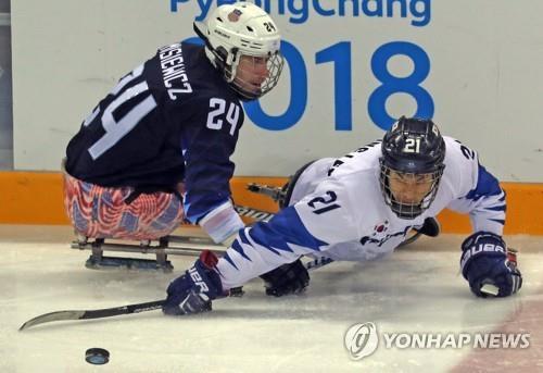 Le Sud-Coréen Lee Ju-seung (à d.) tente de récupérer le palet contre l'Américain Joshua Misiewicz lors d'un match du groupe B de hockey sur luge masculin aux Jeux paralympiques d'hiver de PyeongChang au centre de hockey de Gangneung, dans la province du Gangwon, le 13 mars 2018.