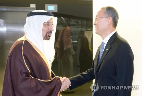 Le ministre de l'Energie Paik Un-gyu serre la main de son homologue saoudien Khalid Al-Falih le 12 mars 2018.