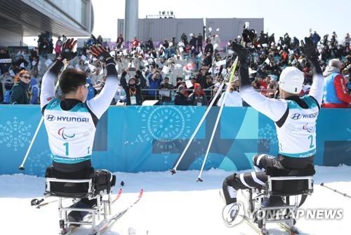 Les Nord-Coréens Ma Yu-chol (à droite) et Kim Jong-hyon saluent le dimanche 11 mars 2018 le public après avoir participé à l'épreuve du 15km assis de ski de fond aux Jeux paralympiques d'hiver de PyeongChang, au centre de biathlon d'Alpensia.