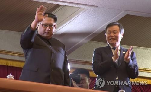 Le dirigeant nord-coréen Kim Jong-un salue de la main le public le dimanche 1er avril 2018 au concert de la troupe artistique sud-coréenne au Grand Théâtre de l'Est de Pyongyang. A droite, se trouve le ministre sud-coréen de la Culture, du Sport et du Tourisme Do Jong-hwan. (Joint Press Corps-Yonhap)