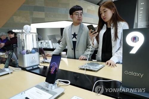 Des visiteurs jettent un coup d'œil au smartphone Galaxy S9 de Samsung Electronics Co. dans un magasin de Séoul, le 16 mars 2018.