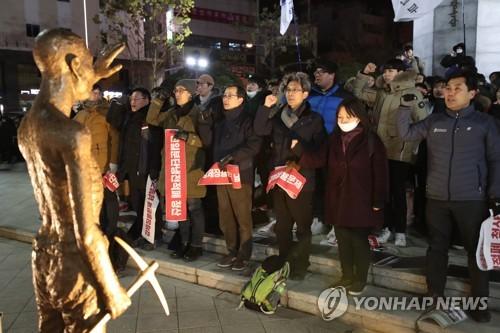 Des activistes manifestent devant une statue temporaire représentant un travailleur coréen le 24 janvier 2018 à Busan.