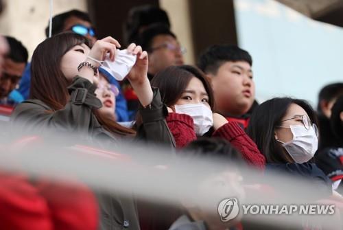 Des spectateurs portent un masque pour se protéger des particules fines le 15 avril 2018 lors du match de football opposant les Pohang Steelers au Gyeongnam FC à Pohang.