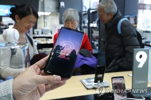 Des visiteurs jettent un coup d'oeil aux smartphones Galaxy S9 de Samsung Electronics Co. dans un magasin à Séoul, le 16 mars 2018.