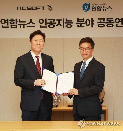 Lee Ki-chang, directeur général de la stratégie managériale de l'agence de presse Yonhap, pose le 16 mai 2018 avec Lee Jay-june, directeur du centre IA de NCSOFT, après avoir conclu un accord pour des recherches conjointes sur les technologies IA.