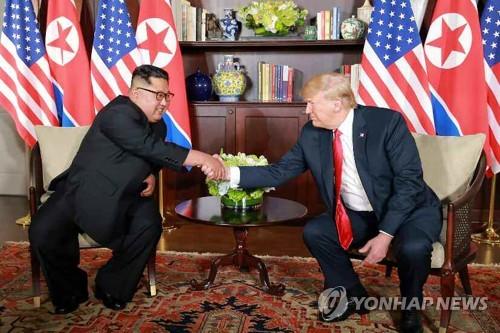 Le dirigeant nord-coréen Kim Jong-un et le président américain Donald Trump échangent une poignée de main le mardi 12 juin 2018 à l'hôtel Capella, sur l'île singapourienne de Sentosa, avant d'entamer leur sommet historique, a rapporté le lendemain le quotidien officiel nord-coréen Rodong Sinmun. (Utilisation en Corée du Sud uniquement et redistribution interdite)