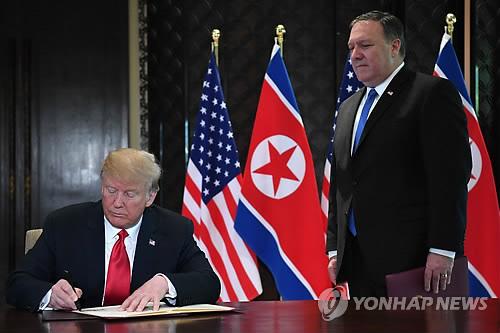 Le président américain Donald Trump signe, sous les yeux de son secrétaire d'Etat, Mike Pompeo, le document commun de son sommet avec le dirigeant nord-coréen Kim Jong-un à Singapour, le 12 juin 2018. © AFP