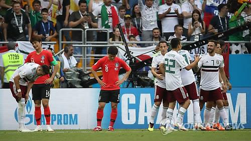Les joueurs mexicains se congratulent après le coup de sifflet final devant des Sud-Coréens déçus par leur deuxième défaite à la Coupe du monde de football au stade de Rostov à Rostov-sur-le-Don, en Russie, le samedi 23 juin 2018 (heure russe).