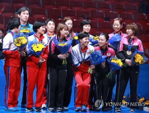 Des joueuses coréennes de l'équipe unifiée posent avec leurs médailles de bronze remportées aux Championnats du monde de tennis de table à Halmstad en Suède le 5 mai 2018.