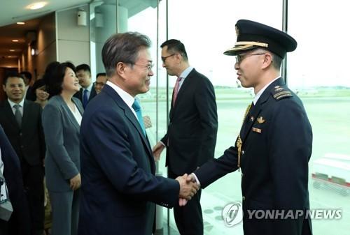Le président Moon Jae-in échange une poignée de main le mercredi 11 juillet 2018 avec un officiel de la délégation singapourienne de bienvenue à son arrivée à l'aéroport international Changi à Singapour.