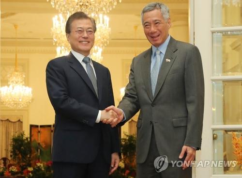 Le président Moon Jae-in échange une poignée de main avec le Premier ministre singapourien Lee Hsien Loong le jeudi 12 juillet 2018 au palais présidentiel Istana à Singapour, lors du sommet bilatéral.