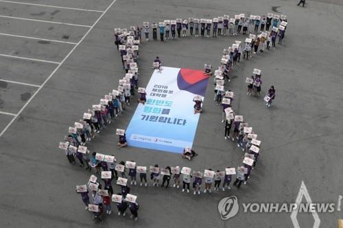 Cette photo, prise le 25 juillet 2018, montre des étudiants sud-coréens venus de l'étranger pour exprimer leur vœux de paix sur la péninsule coréenne à Paju, à environ 50 kilomètres au nord-ouest de Séoul.