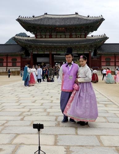 Des touristes en costume traditionnel coréen, hanbok, visitent le palais royal de Gyeongbok, situé dans le centre de Séoul, le 22 avril 2018.