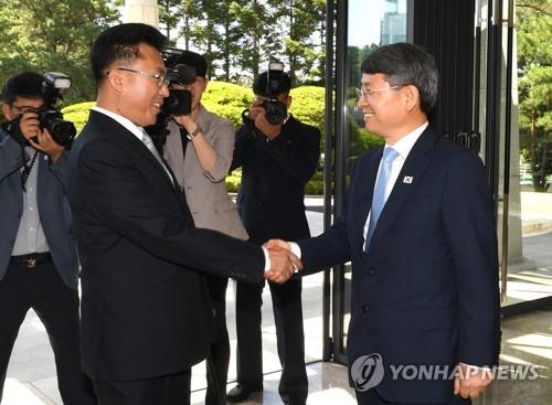 Le vice-ministre du Service forestier coréen (KFS), Ryu Kwang-soo (à droite), échange une poignée de main avec le vice-directeur du bureau forestier du ministère nord-coréen de la Protection de l'environnement, Kim Song-jun, le mercredi 4 juillet 2018, à la Maison de la paix, bâtiment sud-coréen de la maison de la trêve de Panmunjom, avant leur réunion bilatérale sur la coopération dans le secteur forestier. © Ministère de l'Unification