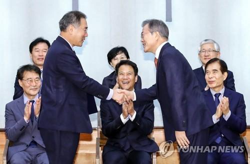 Le président Moon Jae-in échange une poignée de main le mercredi 10 août 2018 avec le nouveau ministre de l'Agriculture, de l'Alimentation et des Affaires rurales après lui avoir remis la lettre de nomination, au bureau présidentiel Cheong Wa Dae.