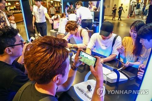 Des jeunes s'amusent avec le tout nouveau smartphone Galaxy Note 9 à un espace de promotion de Samsung Electronics à Séoul, le 12 août 2018. © Samsung Electronics Co.
