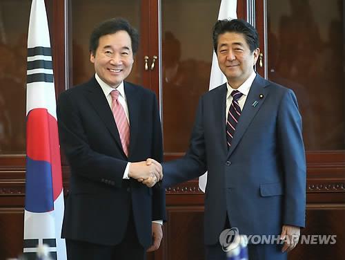 Le Premier ministre Lee Nak-yon échange une poignée de main avec le Premier ministre japonais Shinzo Abe à Vladivostok, en Russie, pendant leur entretien bilatéral, en marge du Forum économique oriental (EEF).
